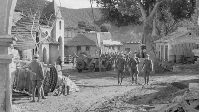 ws shot of military camp as soldiers march on country road - armored truck stock videos and b-roll footage