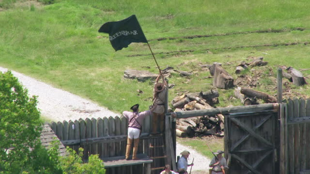 ms ts aerial shot of militia man raises greenbriar flag at fence at fort randolph reenactment / point pleasant, west virginia, united states - american revolution stock videos & royalty-free footage