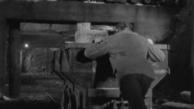 ms shot of miner enters in mine shaft pushing cart away - mine shaft stock videos & royalty-free footage