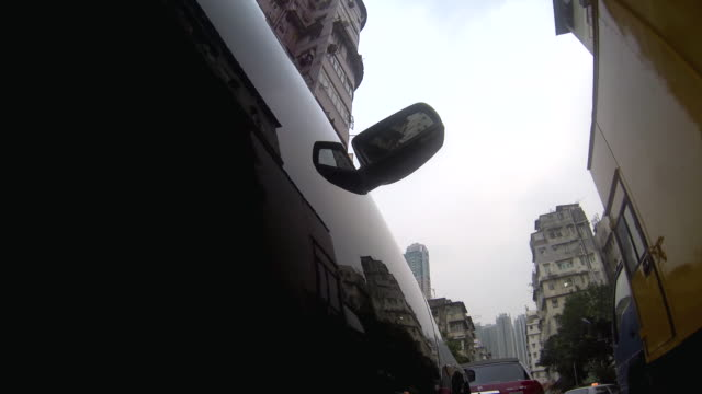CU POV LA Shot of Mirror of car moving on Residential area / Hong Kong, China
