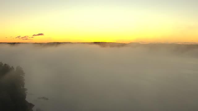 vidéos et rushes de ms aerial shot of  mist on douglas lake at sunrise in cheboygan county and sunrise in sky / michigan, united state - grandiose