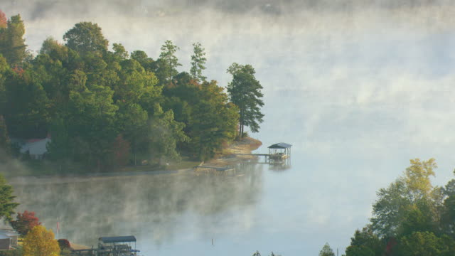 ms aerial shot of mist over lake martin in elmore county with boats docked at shore / alabama, united states - alabama video stock e b–roll