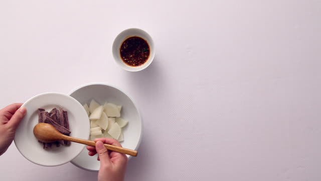 Shot of mixing beef and radish and soy sauce to make Yukgaejang(Korean Spicy Beef Soup)