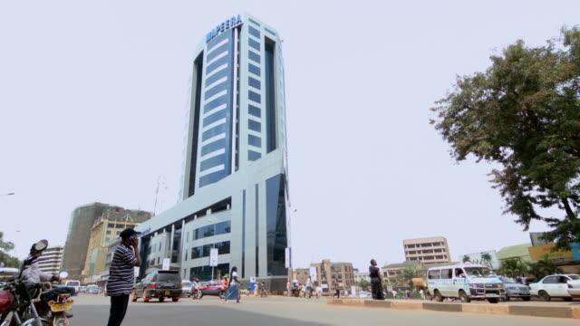 ms shot of modern building and busy street with cars, motorbikes and people / kampala, uganda - ウガンダ点の映像素材/bロール