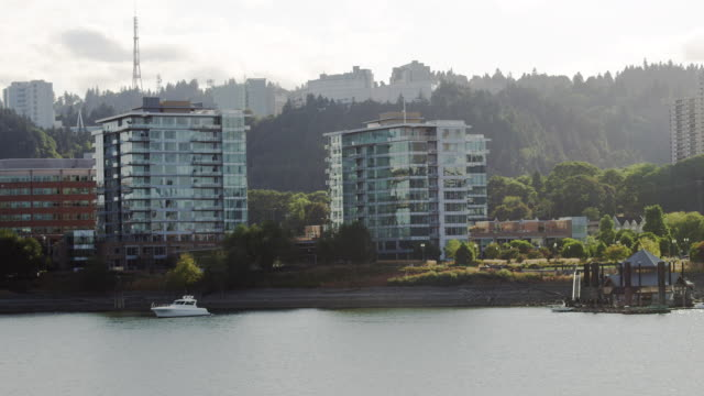 WS Shot of Modern glass apartments on water with boat in front / Portland, Oregon, United States