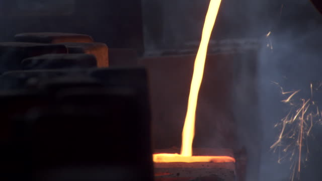 shot of molten iron being poured into cannonball moulds at a foundry. - molten stock videos and b-roll footage