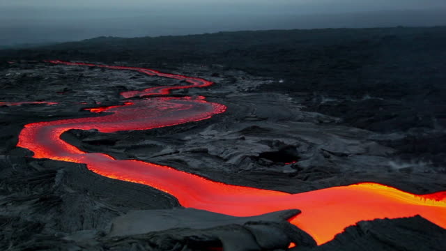 ms t/l shot of molten lava flow going down lava plateau at early morning / big island, hawaii, united states - eruzione video stock e b–roll