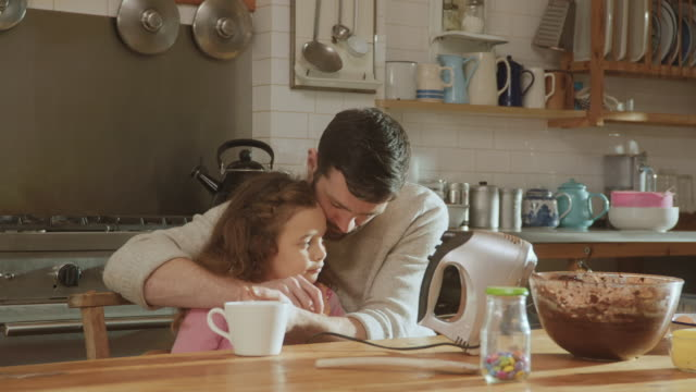 ms shot of moment of affection between father and daughter at kitchen table / london, united kingdom  - tea cup stock videos & royalty-free footage