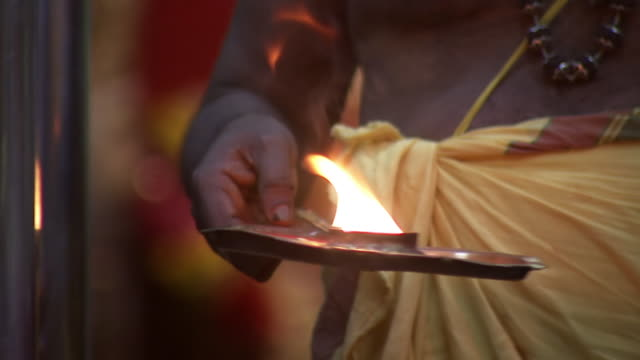 CU TS Shot of monk holding tray with open flame for devotees to hold their hands over it at Sri Mahankali temple / Hyderabad, Andhra Pradesh, India