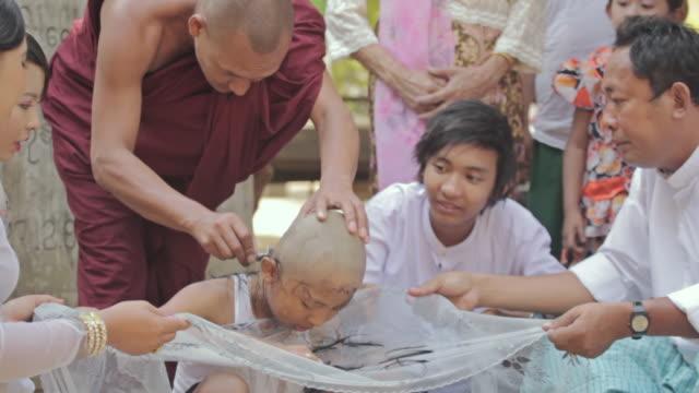 MS Shot of monk shaving a boy's head / Bagan, Mandalay Division, Myanmar