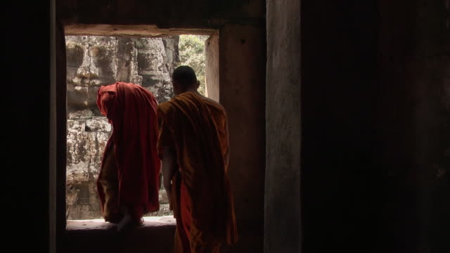 ms shot of monks inside bayon temple at angkor thom and exit temple out of door frame / siem reap, siem reap province, cambodia - 僧点の映像素材/bロール