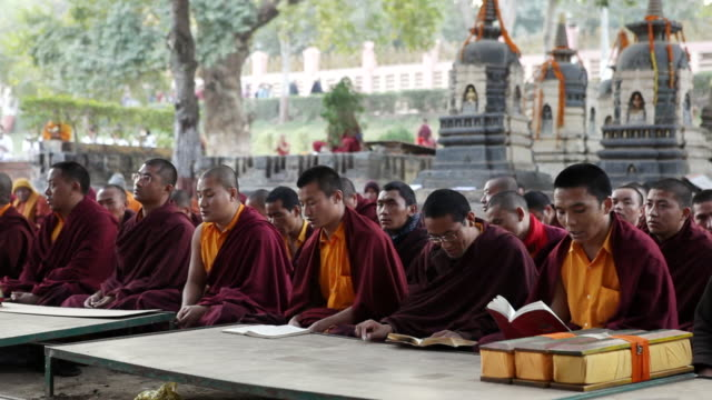 ws pan shot of monks praying in bodhgaya temple / bodhgaya, india  - buddhismus stock-videos und b-roll-filmmaterial