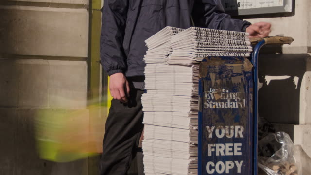"vídeos de stock e filmes b-roll de ""cu t/l shot of moorgate underground entrance in city and commuters take copies of evening standard newspaper from disappearing stack / london, greater london, united kingdom"" - grupo grande de objetos"