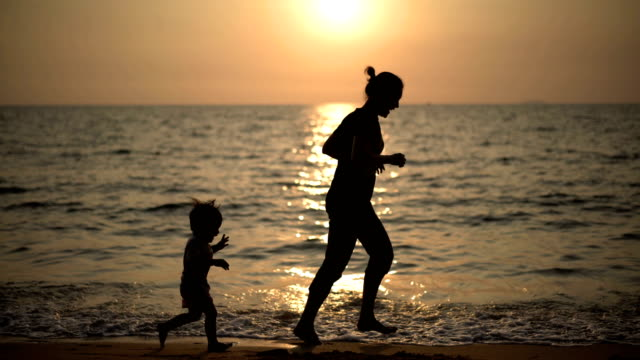 2 shot of mother and baby boy jogging on the beach. - pattaya stock videos & royalty-free footage