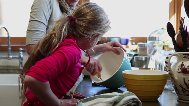 ms shot of mother and daughter baking together in kitchen / lamy, new mexico, united states - lamy new mexico stock videos and b-roll footage