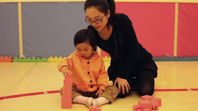MS Shot of mother and daughter playing building blocks in playroom / Xian, China