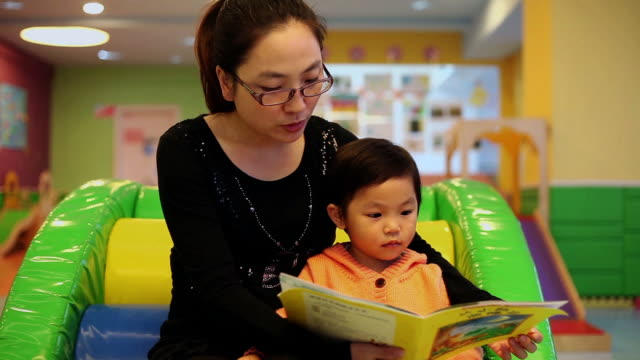 MS Shot of mother and daughter reading book in playroom / Xian, China