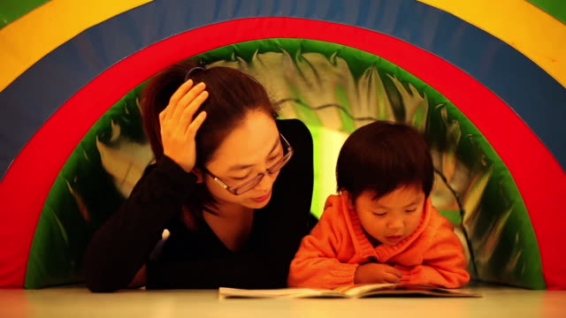 CU Shot of mother and daughter reading book in playroom / Xian, China