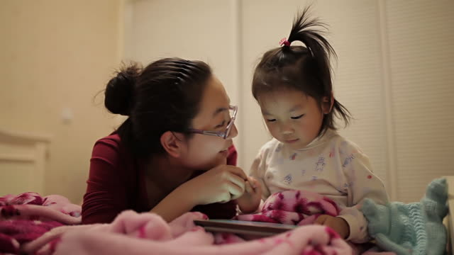 ms shot of mother and daughter spending time together and playing games using digital tablet computer on bed / xi'an, shaanxi, china - family with one child stock videos & royalty-free footage