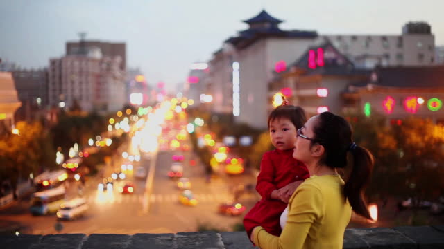 MS Shot of mother and daughter talking on Xian city wall with city traffic at sunset / Xian, China