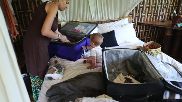 MS TU Shot of mother and her baby packing up their suitcases / Ubud, Bali, Indonesia