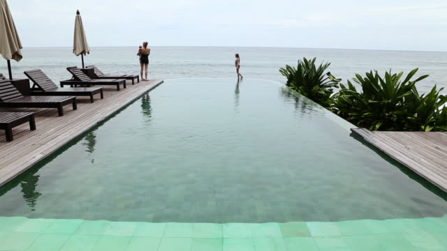 ws shot of mother and her children standing at edge of infinity pool / ubud, bali, indonesia - infinity pool stock videos & royalty-free footage