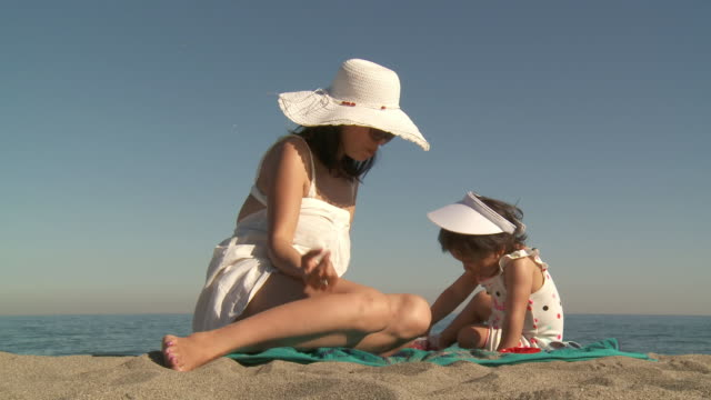 ms shot of mother and his girl eating strawberry on beach / marbella, andalusia, spain - sun visor stock videos and b-roll footage