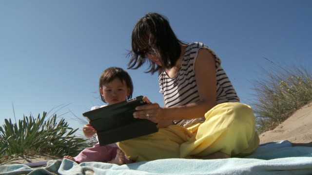 MS Shot of mother and his girl playing with digital tablet on sand dune / Marbella, Andalusia, Spain