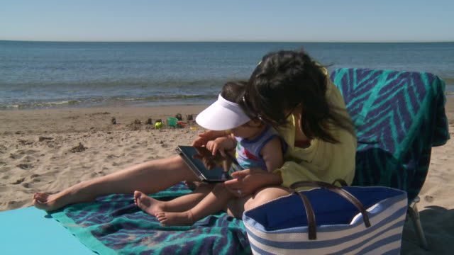 ms shot of mother and his little girl playing with digital tablet at beach / marbella, andalusia, spain - sun visor stock videos and b-roll footage