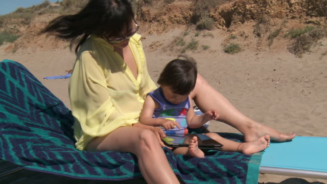 ms shot of mother and his little girl playing with digital tablet at beach / marbella, andalusia, spain - bikini bottom stock videos & royalty-free footage