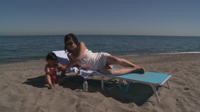stockvideo's en b-roll-footage met shot of mother and his little girl playing with mobil phone at beach - zonnejurk