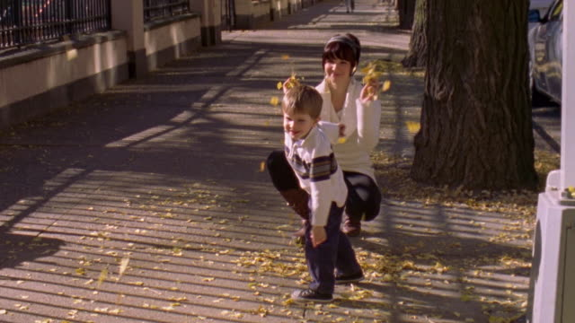 MS ZI Shot of Mother and son throwing leaves around on sidewalk in west village in autumn / New York, United States