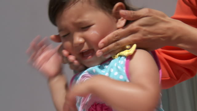 CU Shot of mother applying sunscreen to child / Marbella, Andalusia, Spain
