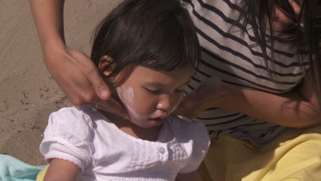 shot of mother applying sunscreen to child. - sun cream stock videos & royalty-free footage