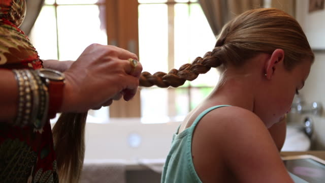 CU Shot of mother braiding her daughters hair / Lamy, New Mexico, United States