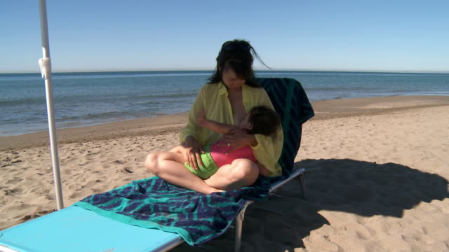 vidéos et rushes de ms shot of mother breastfeeding girl at beach / marbella, andalusia, spain - allaiter