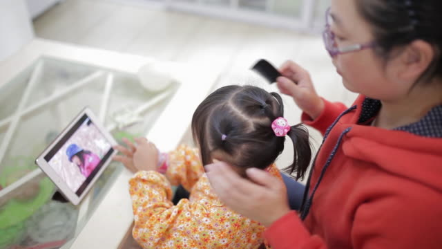 ms shot of mother brushes her daughter hair, daughter watching movie with mobile phone / xi'an, shaanxi, china - hair band stock videos & royalty-free footage