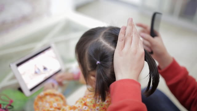 stockvideo's en b-roll-footage met ecu shot of mother brushes her daughter hair, daughter watching movie with a mobile phone / xi'an, shaanxi, china - kammen