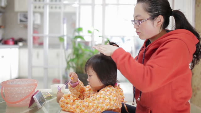 CU Shot of Mother brushes her daughter hair, daughter watching movie with mobile phone / Xi'an, Shaanxi, China