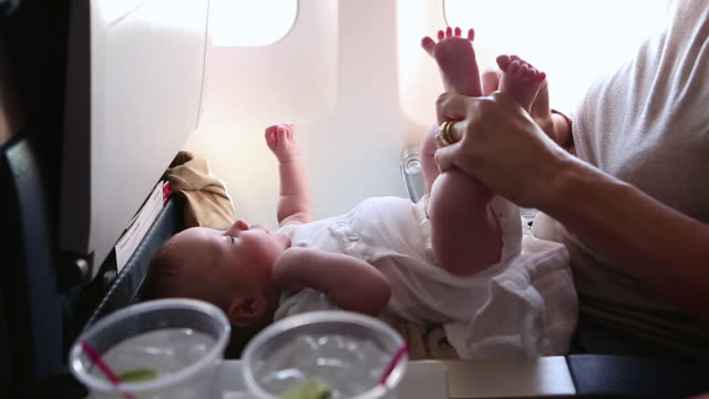 cu zi shot of mother changing her baby's diaper on airplane / st. simons island, georgia, united states - nappy stock videos & royalty-free footage