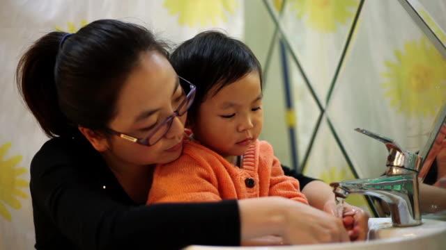 cu shot of mother helping daughter washer her hands / xian, china - お手洗い点の映像素材/bロール