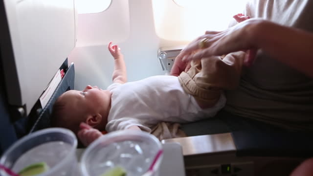cu shot of mother holding her baby on airplane / st. simons island, georgia, united states - accudire video stock e b–roll
