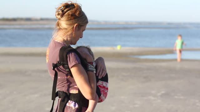 ms shot of mother holding her baby on beach / st simon's island, georgia, united states - baby carrier stock videos & royalty-free footage