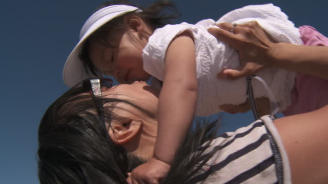 shot of mother lifting daughter on beach. - sun visor stock videos & royalty-free footage