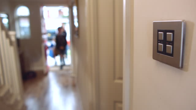 MS R/F Shot of Mother returns home from school run with children with light switch In foreground