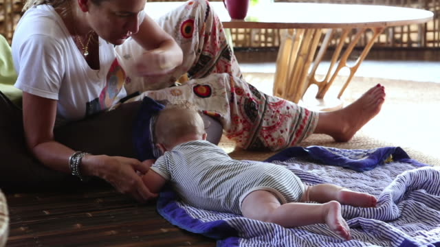 ms tu shot of mother sitting with her baby boy / ubud, bali, indonesia - baby blanket stock videos and b-roll footage