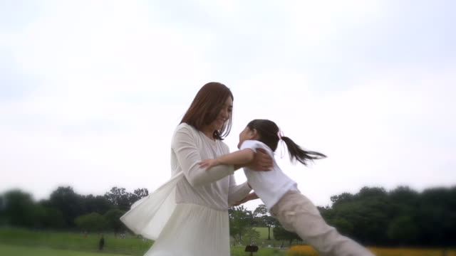 ms slo mo shot of mother spinning young daughter / seoul, south korea - grass family stock videos & royalty-free footage