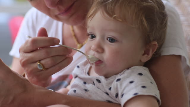 cu shot of mother spoon feeding her baby / st simon's island, georgia, united states - spoon stock videos & royalty-free footage