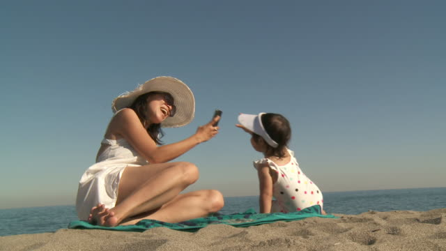 ms shot of mother take picture of his little girl on beach / marbella, andalusia, spain - sun visor stock videos and b-roll footage