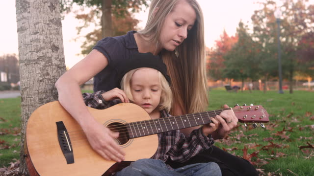 MS Shot of mother teaching her son to strum and play guitar in park / Beaverton, Oregon, United States